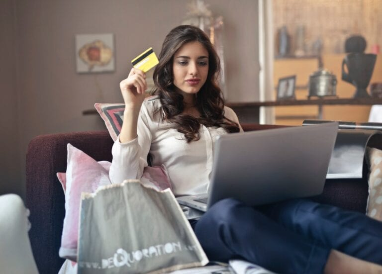 woman holding a credit card browsing for the best selling service
