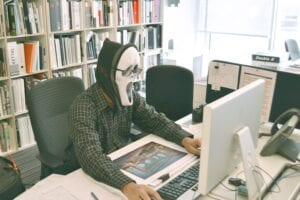 Masked man typing in his computer symbolizing rip-off review writers