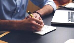 An applicant writing down his KSA narrative statement