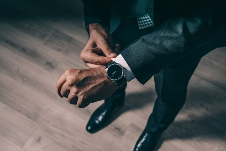 Signs of an effective leadersship is when one comes on time as signified by a man wearing a suit fixes his watch
