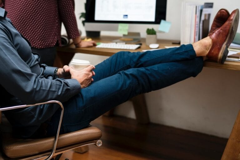 A male employee resting his feet in his desk that shows work procrastination