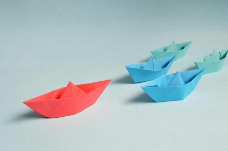 Five paper boats with one boat leading the pack to signify an excellent leader
