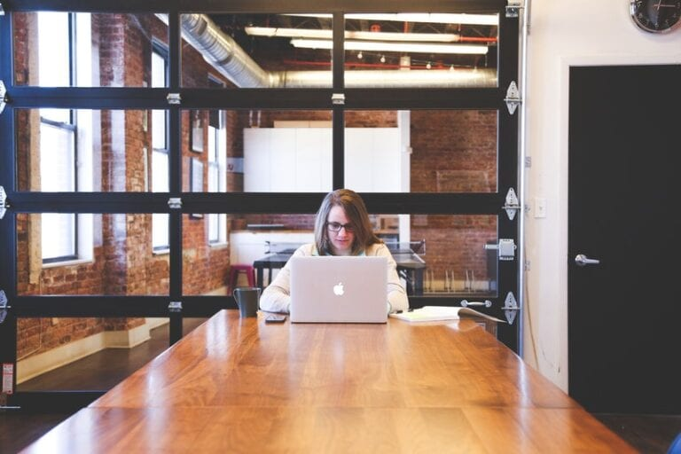 A woman writing a winning resume using her laptop in a wooden table and a room full of glass walls