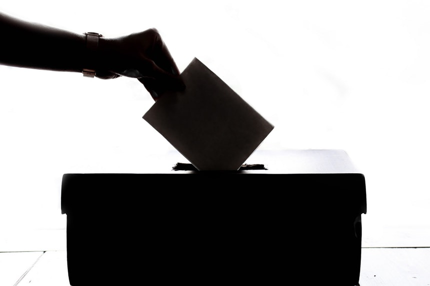 A Voter Placing His Votes In A Ballot Box.