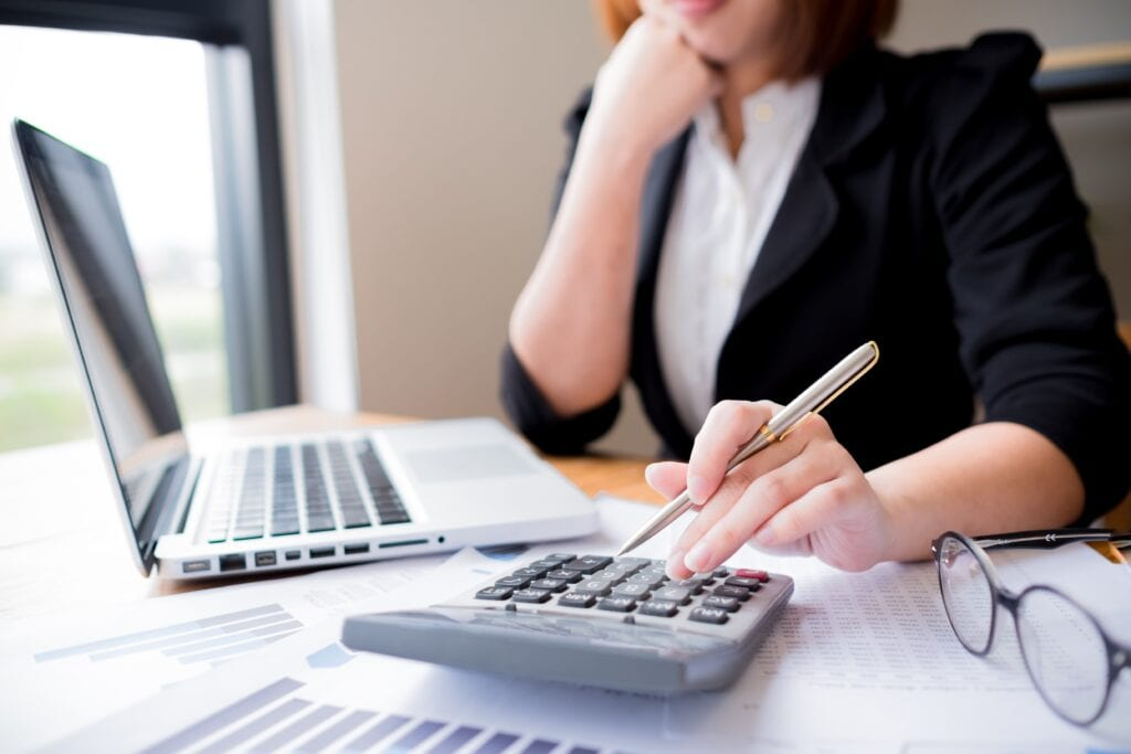 A Female Accountant Viewing Chief Accounting Officer Resume Example On Her Laptop While Using The Calculator