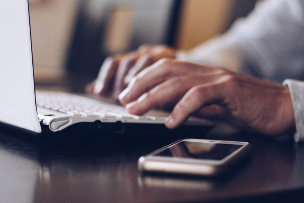 Man Using His Laptop To Browse For Fundraising Manager Resume Example Online