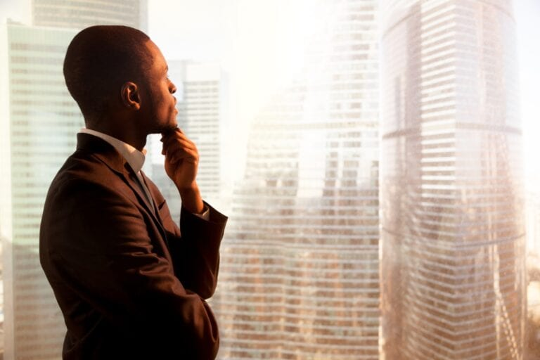 An employee looking out the window and thinking how to rekindle his love for job