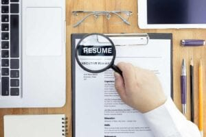 How to write a narrative resume: A hand holding a magnifying glass over a narrative resume sample