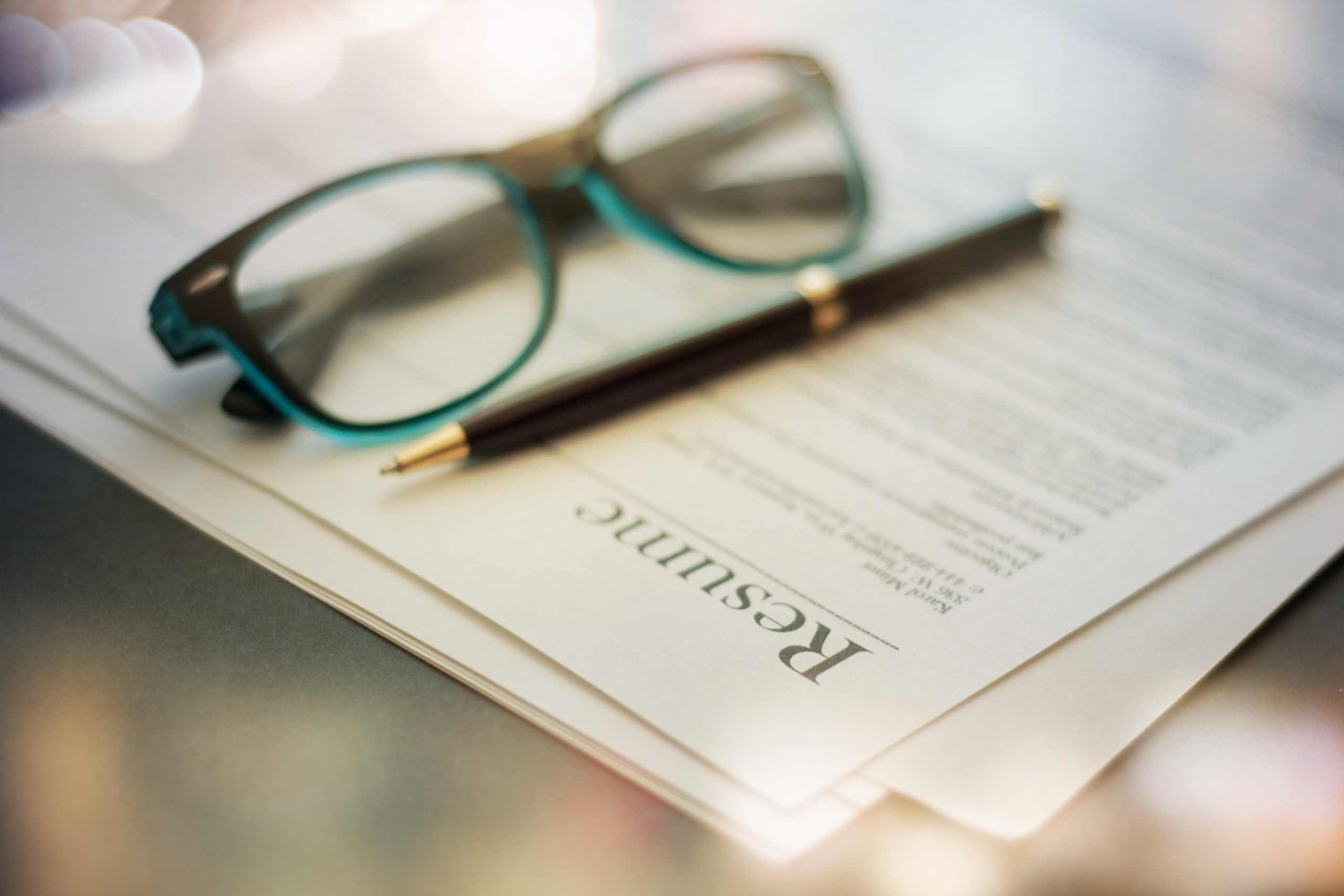 How to write a narrative resume: An eyeglass and pen on top of a narrative resume sample