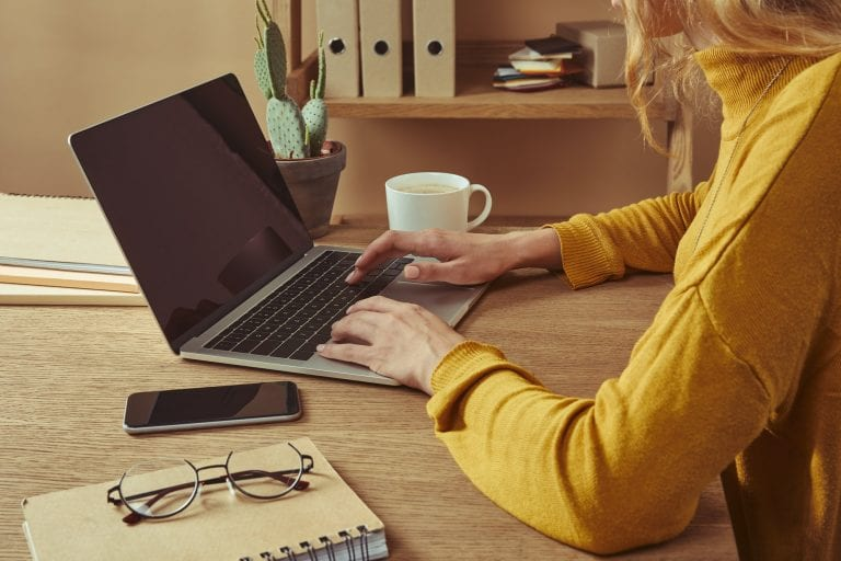 image of woman using laptop to prepare writing her resume online