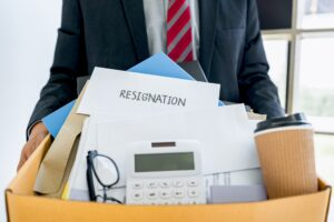 employee carrying all his personal belongings into a brown cardboard box with his resignation letter