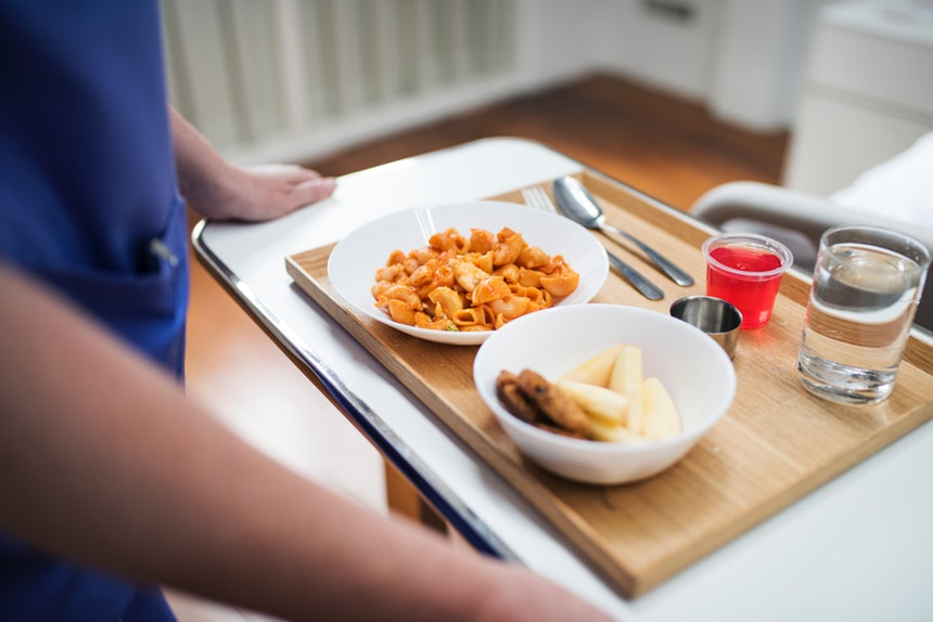 Nurse with successful cover letters delivering food to patient