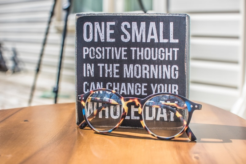 A quote about positive thinking and an eyeglass above a wooden table