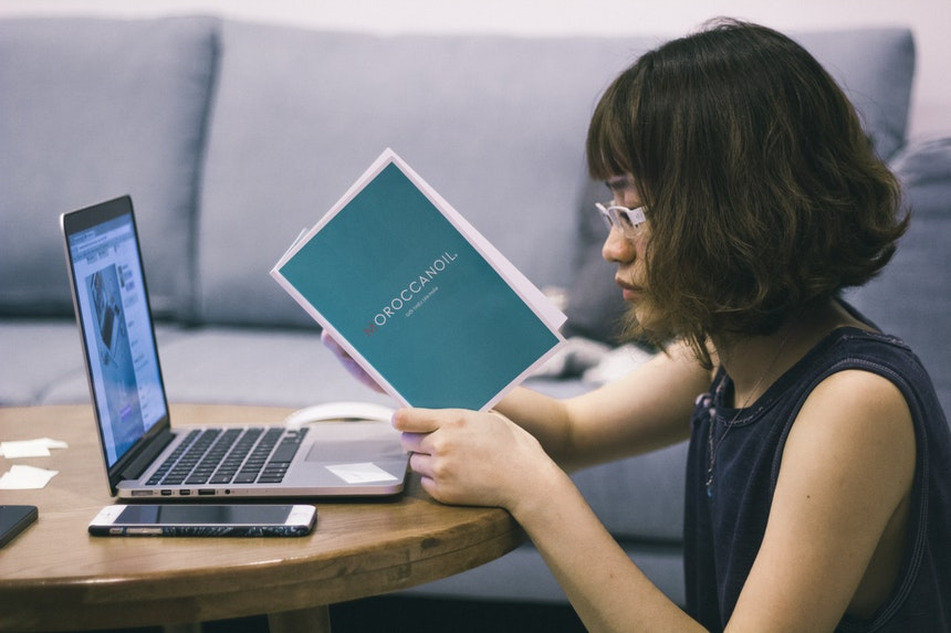 A woman sitting down while reading a book to achieve career success
