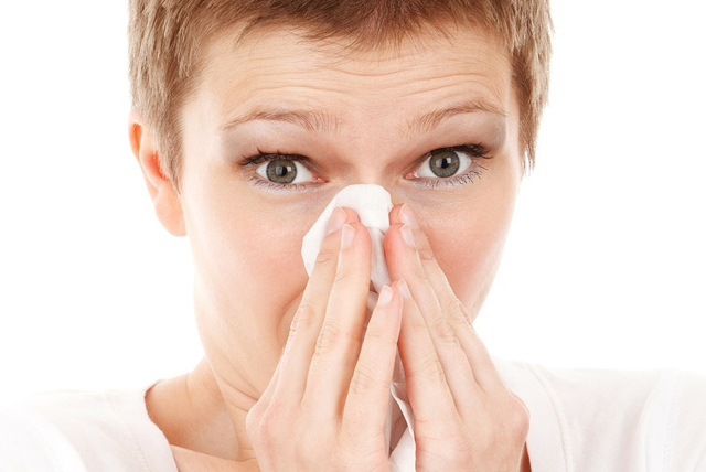 A Headshot Picture Of A Woman Covering Her Nose With A Tissue