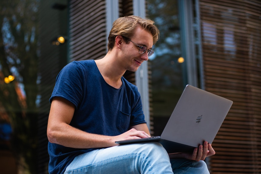 A man wearing a dark colored shirt searching for a free resume review online in his laptop