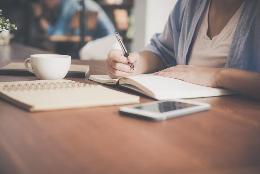 A job seeker writing a resume critique checklist.