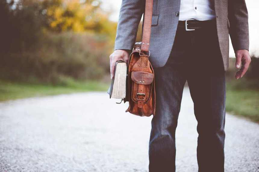 A man wearing a suit while carrying his bag and pursue career change