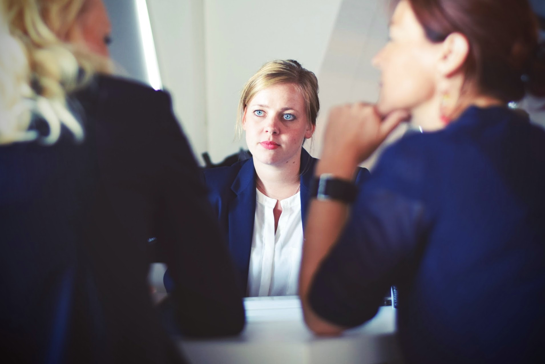 Salary Negotiation tips: two brown haired female interviewers face another blonde female applicant
