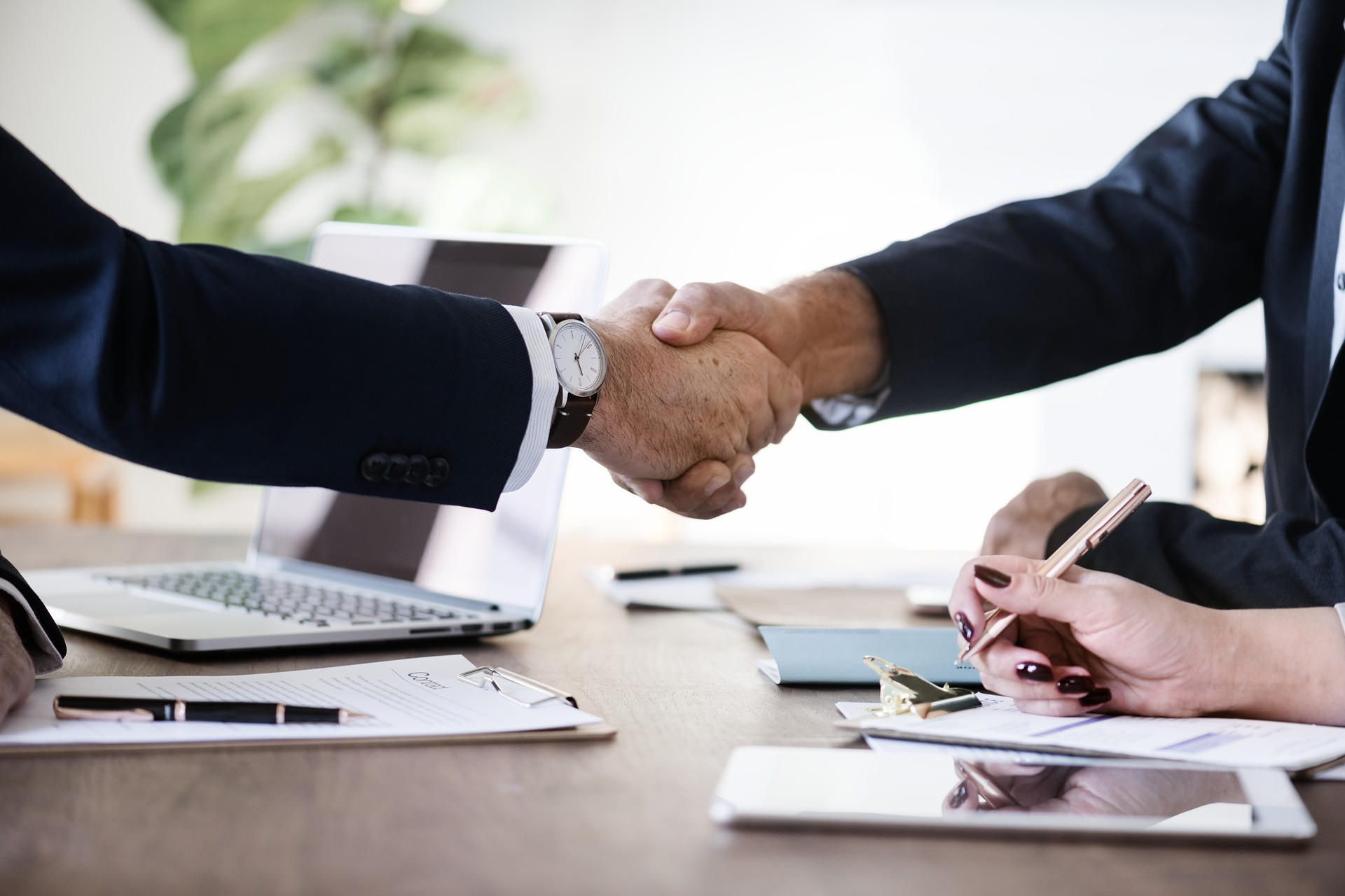 Two arms shaking opposite hands on top of a table with laptop, paper, and pen after a salary negotiation.