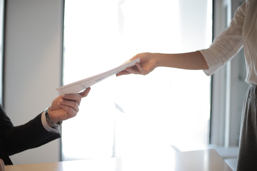 A job applicant is handing his application after getting urgent resume writing services
